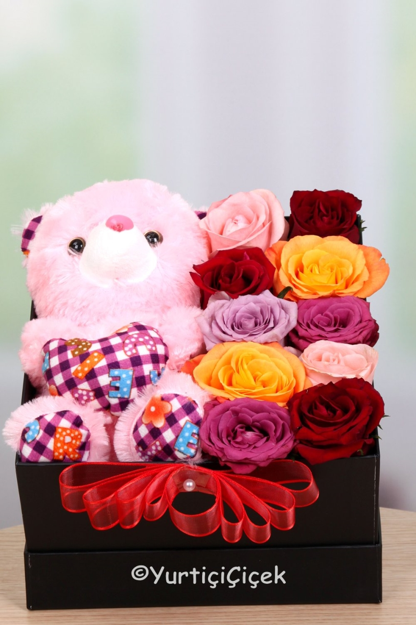 Black box with colorful roses made arrangements with a teddy bear and how much you love her and how special you feel you have found.