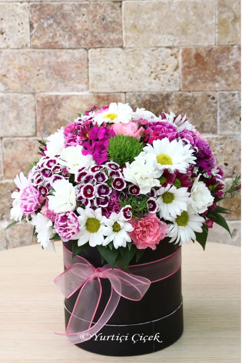 Arrangement prepared from every color of wildflowers in a round box will color every living environment.